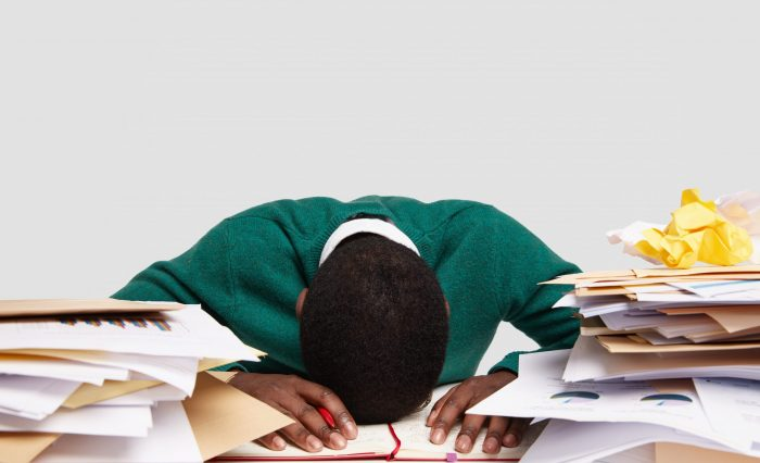 Stressful workaholic keeps head down on desk, feels tired and overworked, has much work, prepares for upcoming exam, writes information in diary, studies documentation, isolated on white wall